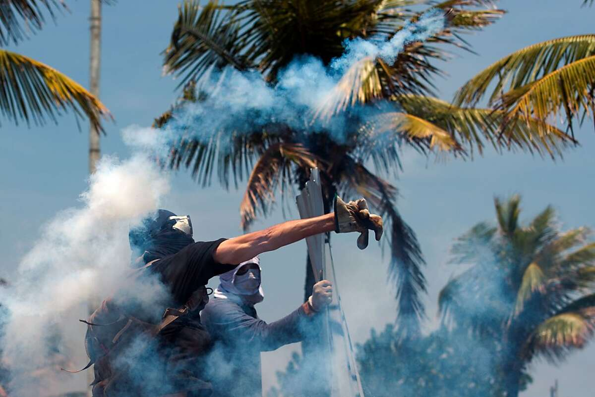Protesters hurl tear gas bombs back at police in front of the Rio de Janeiro hotel where Brazil's National Petroleum Agency was auctioning off drilling rights to one of the world's largest offshore oil discoveries. China's CNOOC and CNPC, Anglo-Dutch giant Royal Dutch Shell and France's Total won the auction to join Brazilian state operator Petrobras in developing the huge