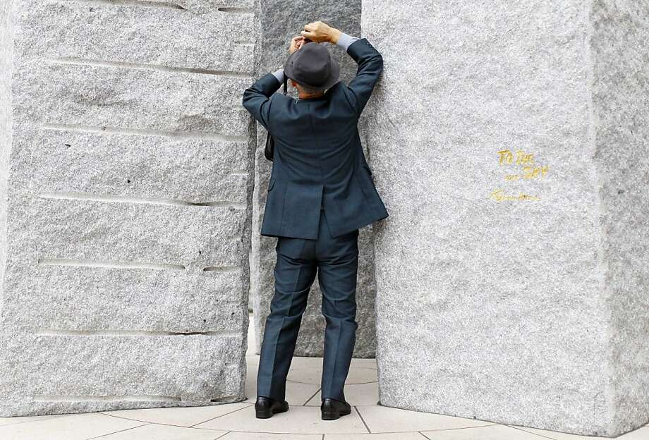 Through a gap in monolithic stones,a dapper man snaps a picture of the Tokyo Skytree, a broadcasting, restaurant and observation tower. Photo: Junji Kurokawa, Associated Press