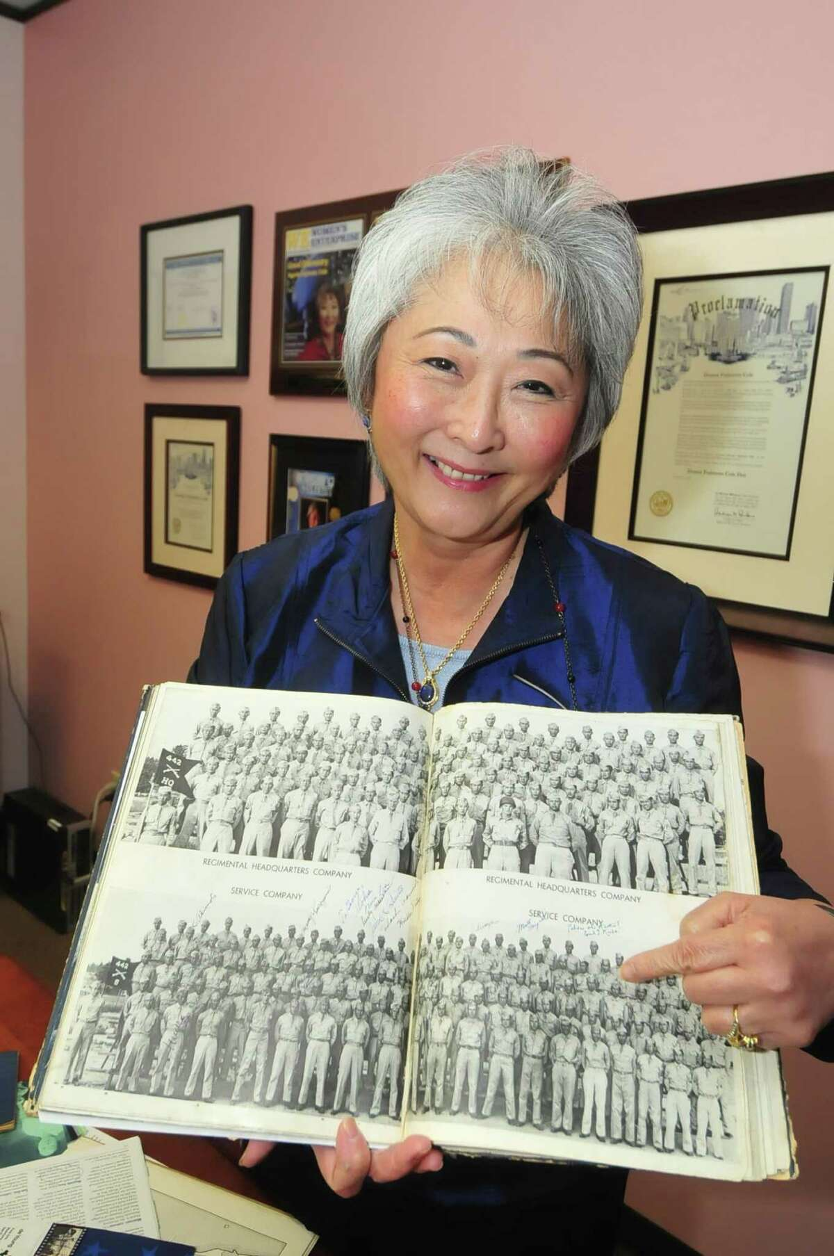 Donna Cole shows where her father is in a 1943 photo of the Army 442nd Combat Team, which has been honored for its role in World War II.