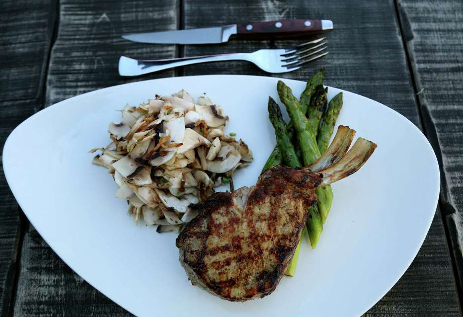 A pork chop, with asparagus & shaved mushroom salad at Eleven XI. Photo: Karen Warren, Staff / © 2013 Houston Chronicle