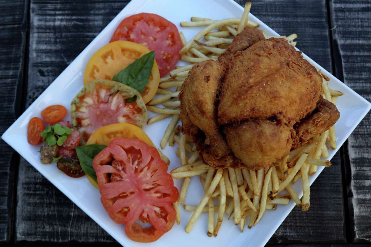 A whole fried game hen, with heirloom tomatoes and french fries at Eleven XI, 607 West Gray, Thursday, Oct. 17, 2013, in Houston. ( Karen Warren / Houston Chronicle )