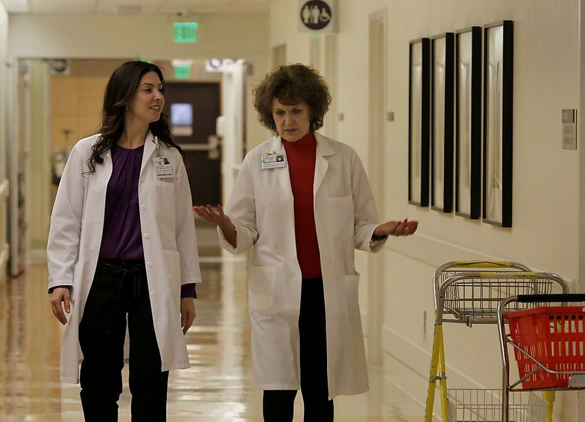 """Professor Barbara J. Drew from the UCSF School of Nursing (right) and Tina Mammone RN, the Director of Clinical Operations for Nursing talk as they head towards an ICU unit at the Medical Center Thursday October 17, 2013 in San Francisco, Calif. UCSF nurse researchers are at the forefront of studying and trying to resolve a problem known as """"alarm fatigue"""" which is the unintended consequence of nurses becoming desensitized to all the alarms designed to keep patients alive."""