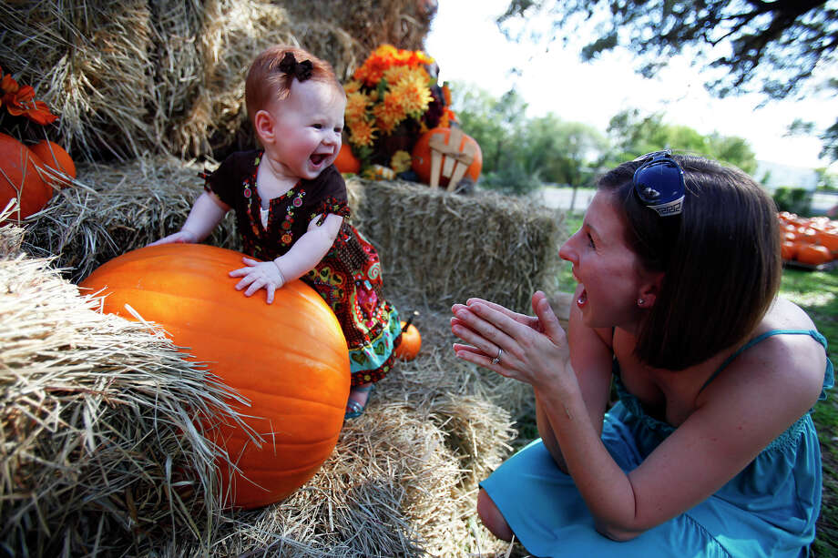 Janice Derington of Schertz, right, helps her daughter, 6-month-old Hannah Derington, pose for a picture on the first day of the pumpkin patch at Bracken United Methodist Church, 20377 FM 2252.