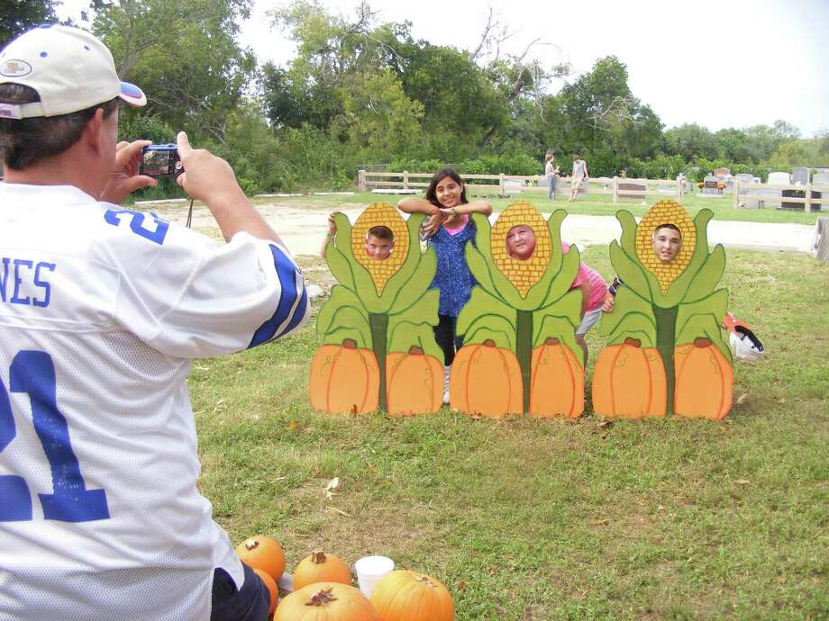 Tony Clements snaps a photo of his daughter Trina, 11, posing above Michele Hundza (center) and her sons, Joe, 12 (left), and Zachary, 9, atthe St. Paul Evangelical Church pumpkin patch, 108 S. Main St. in Cibolo.