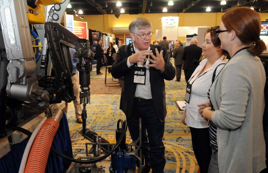 Carl Thornton, from left, Supply Chain Manager for Delta SubSea in Montgomery,   talks about the HD 27 System II with Salina Hoover and Judie Hale, both of Spring who work for Anadarko's Supply Chain for Contracts & Procurement for their Mozambique project, during the Deep Offshore Technology International Conference & Exhibition 2013 at The Woodlands Waterway Marriott Hotel & Convention Center in The Woodlands on Tuesday. Photo: For The Chronicle