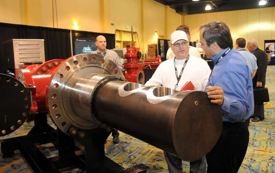 Robert Vandygrift, from left, Unit Trainer for the Coker Dept. at Phillips 66 Los Angeles Refinery Carson Plant, talks with Miguel Lopez, Director of Business Development - Latin America Oil & Gas Systems for I Curtiss Wright Flow Control Company of Houston during the Deep Offshore Technology International Conference & Exhibition 2013 at The Woodlands Waterway Marriott Hotel & Convention Center in The Woodlands on Tuesday. Photo: For The Chronicle