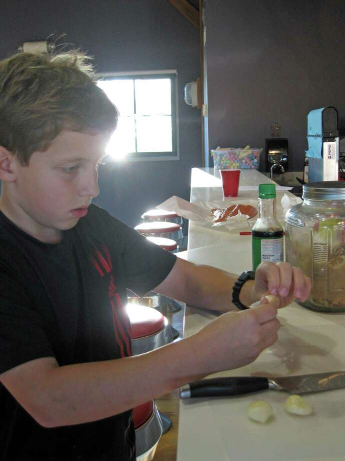 Cole Prochilo focuses as he prepares garlic for Salmon with Ginger Glaze in Chez Neena's Culinary Arts Series at the New Canaan Outback. Photo: Contributed Photo / New Canaan News