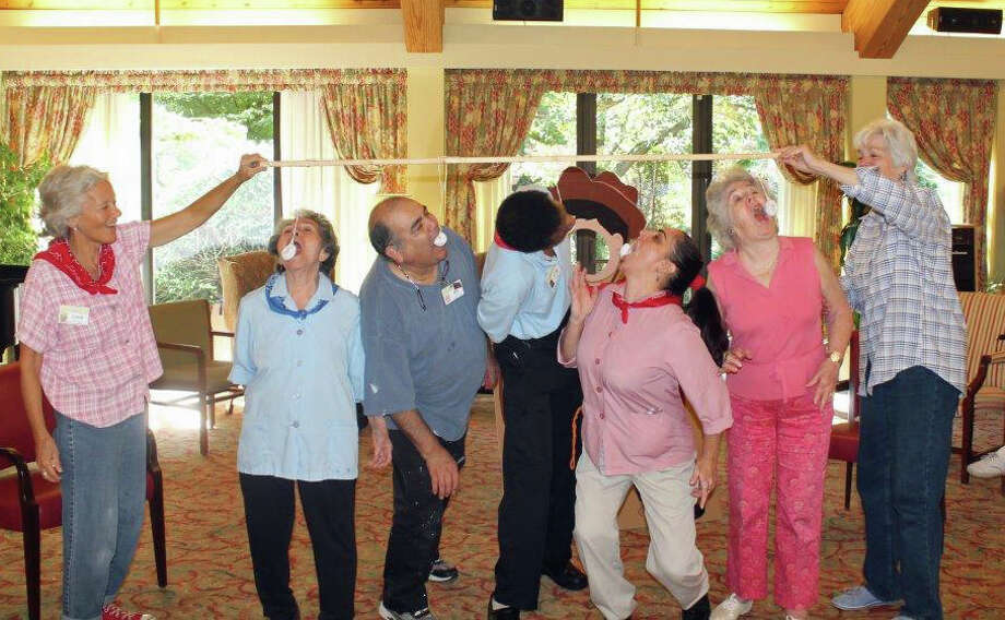 New Canaan Inn staff ìstretch for donutsî at the Harvest Country Fair. Photo: Contributed Photo / New Canaan News