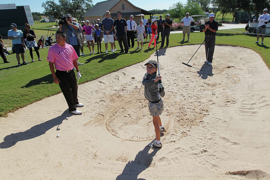 Professional golfers Esteban Toledo, left in pink, and Phil Blackmar, right in back, watch as nine-year-old Sky Sudberry, of The Woodlands, Texas hits a bunker shot before the start of the GENCO Junior Pro-Am at TPC San Antonio, Tuesday, Oct. 22, 2013. The AT&T Championship Tournament will start on Friday and run through Sunday. Photo: Jerry Lara, San Antonio Express-News / ©2013 San Antonio Express-News