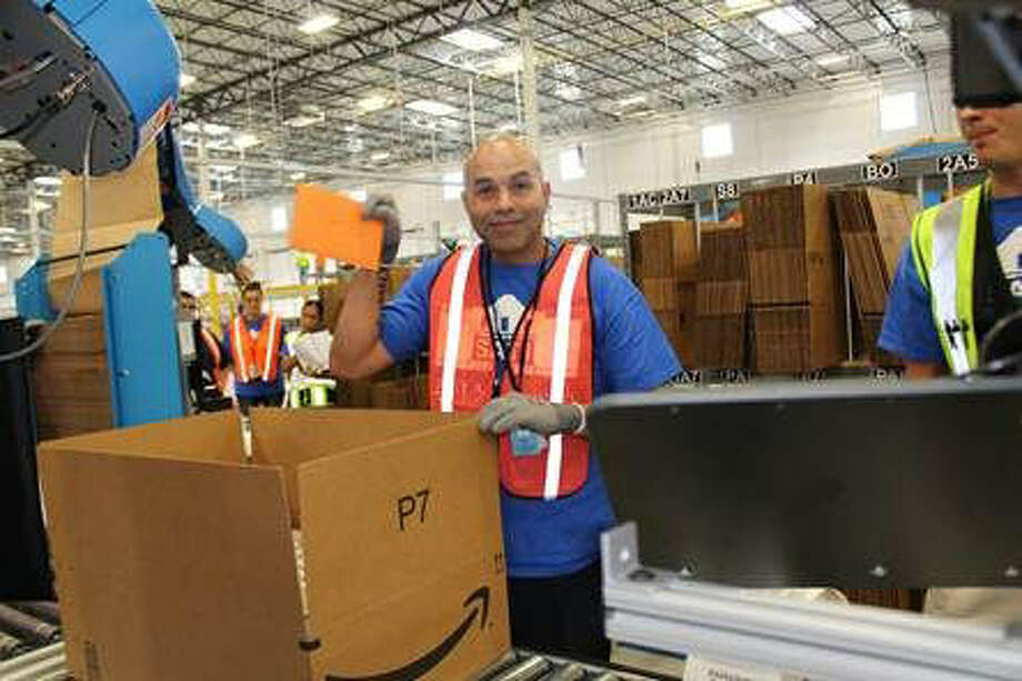 An Amazon.com employee loads a vanity stool into a shipping case, the first such order to leave Amazon's new plant in Schertz. Photo: Courtesy Photo