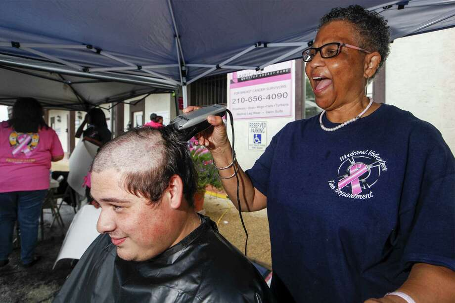"""Barbara Rice (right) reacts while shaving the head of Windcrest volunteer firefighter Brandon Connor during the Oct. 16 """"Bald For Breast Cancer"""" fundraiser benefiting The SLEW Wellness Center. The event was held at Lingerie Line in Windcrest. Photo: Marvin Pfeiffer / NE Herald"""