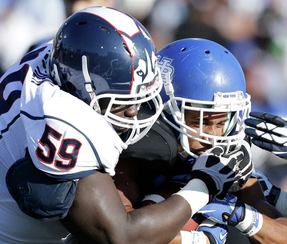 Connecticut defensive tackle Shamar Stephen (59) tackles Buffalo running back Devin Campbell during the first half of an NCAA college football game on Saturday, Sept. 28, 2013, in Buffalo, N.Y. (AP Photo/Mike Groll) Photo: Mike Groll, Associated Press / Associated Press