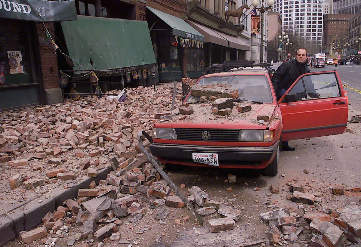 Paul Riek is pictured checking his car in Pioneer Square to see if it starts after a magnitude 6.8 quake hit Seattle and the region on Feb. 28, 2001. (AP Photo/Stevan Morgain)
