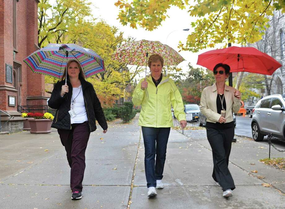 From left, DEC employees Amy KcKelvey of Rotterdam, Sandra King of Saratoga Springs and Maryann Mroz of Colonie cover themselves from the rain during a walk down State St. Tuesday lunchtime, Oct. 22, 2013, in Albany, N.Y.  (Lori Van Buren / Times Union) Photo: Lori Van Buren / 00024340A