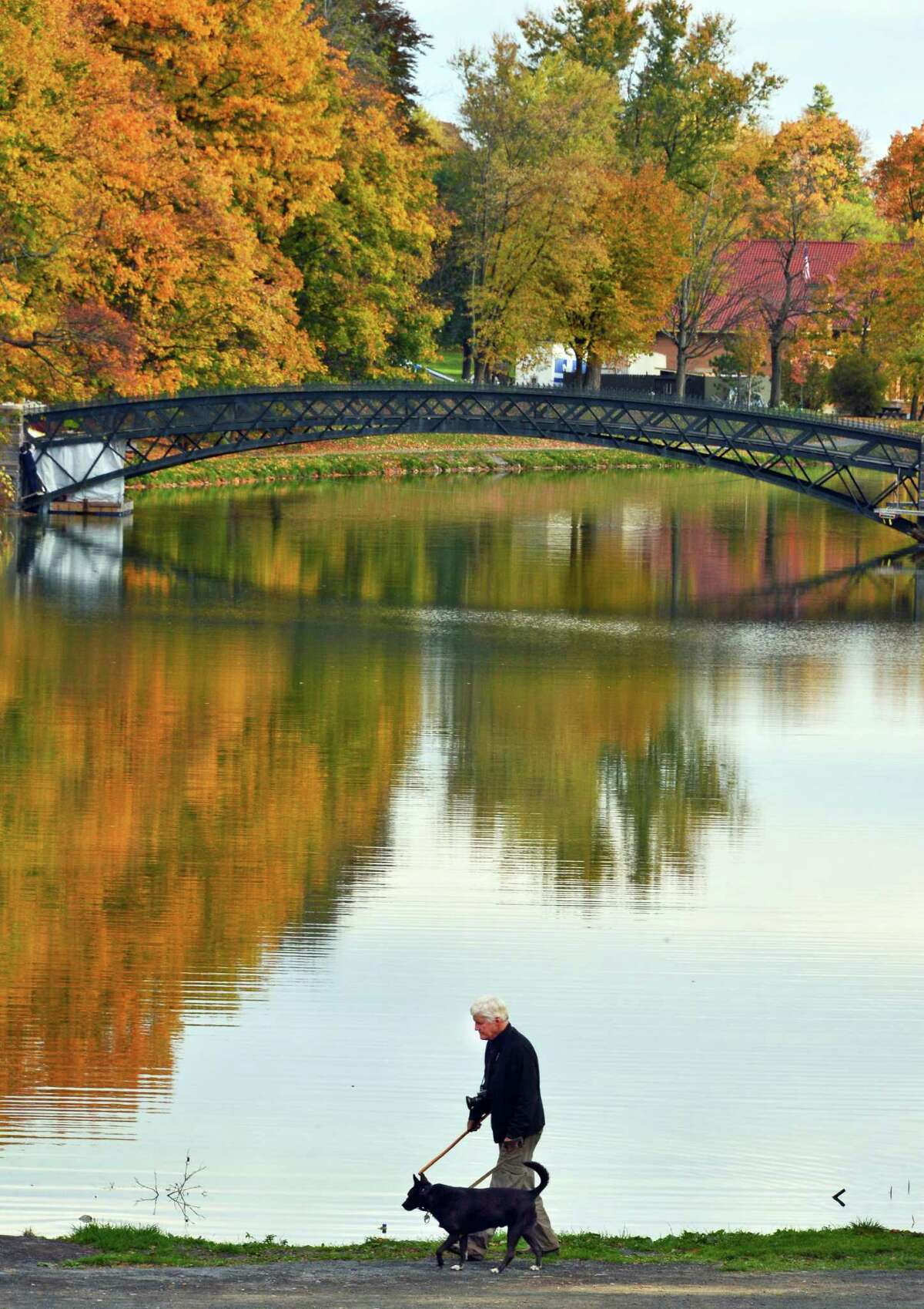 Willard Bridgham walks his dog Booker T around the lake in Washington Park Tuesday Oct. 22, 2013, in Albany, NY. (John Carl D'Annibale / Times Union)