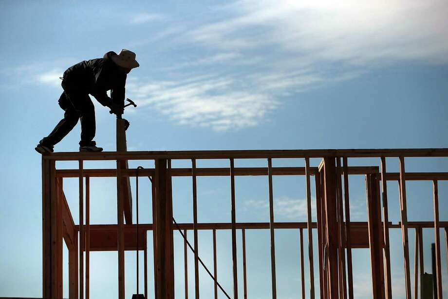 NEW YORK, NY - OCTOBER 22:  Builders construct new homes in an area that was heavily damaged by fire in Hurricane Sandy on October 22, 2012 in the Breezy Point neighborhood of the Queens borough of New York City. As the one-year anniversary of Hurricane Sandy approaches, many residents of the Rockaways and neighboring Breezy Point are reflecting on the progress made over the past year while acknowledging the problems still evident. While the area has made great headway with rebuilding and renovations to the iconic beach communities, the storm devastated much of the area with severe flooding and wind damage. Hurricane Sandy made landfall on October 29 near Brigantine, New Jersey and affected 24 states from Florida to Maine and cost the country an estimated $65 billion.  (Photo by Spencer Platt/Getty Images) ORG XMIT: 185402411 Photo: Spencer Platt / 2013 Getty Images
