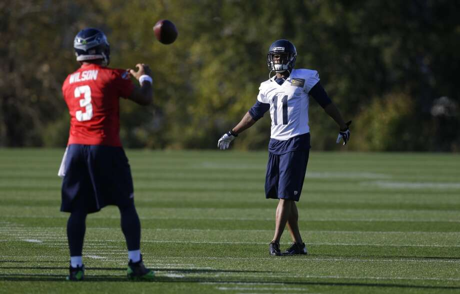Seattle Seahawks wide receiver Percy Harvin (11) returns the ball to Seahawks quarterback Russell Wilson (3) as they take part in an NFL football practice, Tuesday, Oct. 22, 2013, in Renton, Wash. It was Harvin's first full team practice since he injured his hip during the off-season. Photo: Ted S. Warren, Associated Press
