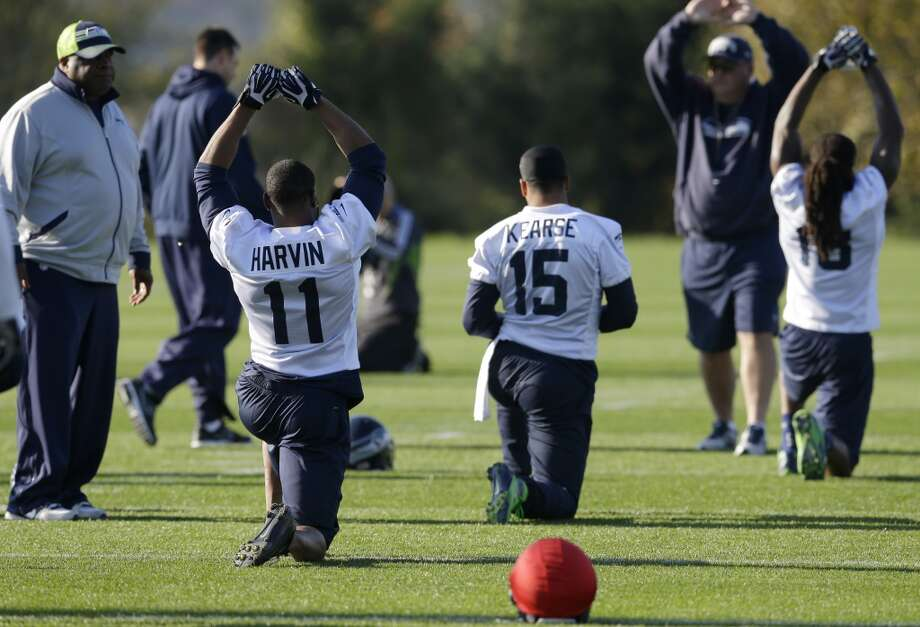 Seattle Seahawks wide receiver Percy Harvin (11) stretches with teammates as wide receivers coach Kippy Brown looks on at left, at the start of NFL football practice, Tuesday, Oct. 22, 2013, in Renton, Wash. It was Harvin's first full team practice since he injured his hip during the off-season. Photo: Ted S. Warren, Associated Press