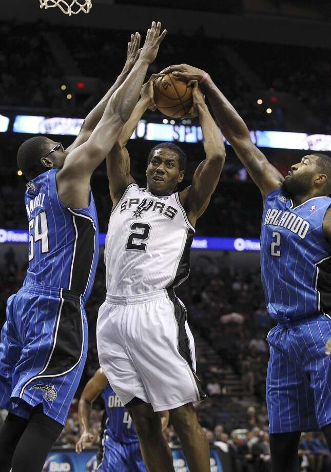 Spurs' Kawhi Leonard attempts to drive the basket between the Orlando Magic's Jason Maxiell (54) and Kyle O'Quinn (02) during their preseason game at the AT&T Center on Tuesday, Oct. 22, 2013. Photo: Kin Man Hui, San Antonio Express-News