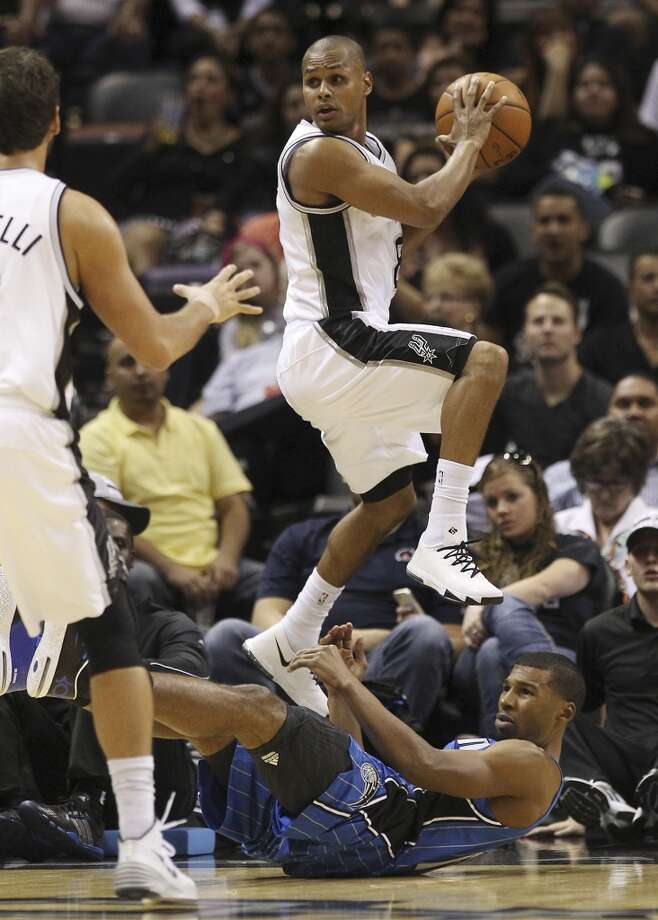 Spurs' Patty Mills leaps over Orlando Magic's Ronnie Price during their preseason game at the AT&T Center on Tuesday, Oct. 22, 2013. Photo: Kin Man Hui, San Antonio Express-News