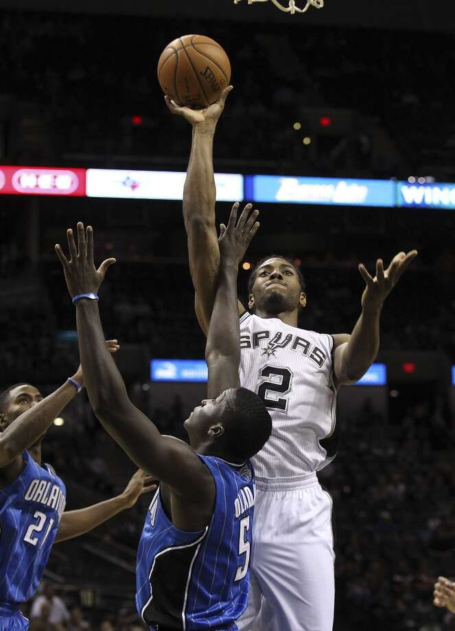 Spurs' Kawhi Leonard goes up for a shot over Orlando Magic's Victor Oladipo during their preseason game at the AT&T Center on Tuesday, Oct. 22, 2013. Photo: Kin Man Hui, San Antonio Express-News