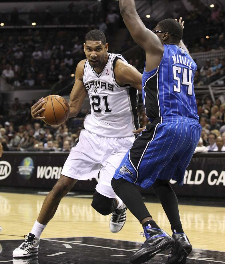 Spurs' Tim Duncan attempts to drive the basket against the Orlando Magic's Jason Maxiell during their preseason game at the AT&T Center on Tuesday, Oct. 22, 2013. Spurs prevailed 123-101. Photo: Kin Man Hui, San Antonio Express-News