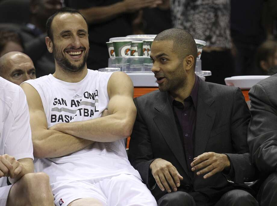 Spurs' Manu Ginobili (left) and Tony Parker share a laugh on the bench during the Orlando Magic preseason game at the AT&T Center on Tuesday, Oct. 22, 2013. Spurs prevailed 123-101. Photo: Kin Man Hui, San Antonio Express-News