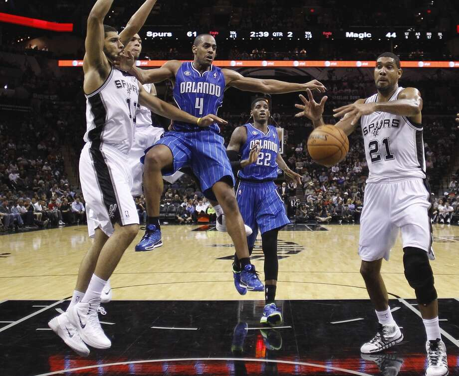 Orlando Magic's Arron Afflalo (4) is stripped of the ball by San Antonio Spurs' Jeff Ayres (11) as Tim Duncan (21) grabs the loose ball during the first half of a preseason NBA basketball game, Tuesday, Oct. 22, 2013, in San Antonio. Photo: Eric Gay, Associated Press
