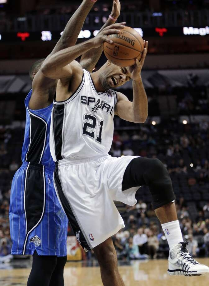 San Antonio Spurs' Tim Duncan (21) reacts as he fouled by Orlando Magic's Kyle O'Quinn, left, during the first half of a preseason NBA basketball game, Tuesday, Oct. 22, 2013, in San Antonio. Photo: Eric Gay, Associated Press