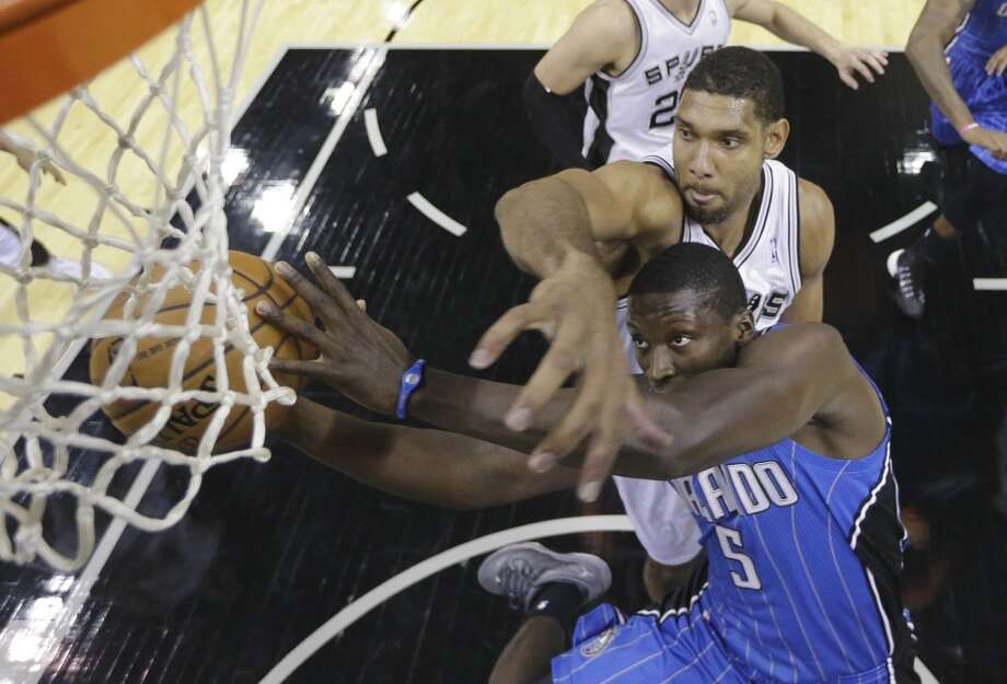 Orlando Magic's Victor Oladipo (5) is defended by San Antonio Spurs' Tim Duncan as he drives to the basket during the first half of a preseason NBA basketball game, Tuesday, Oct. 22, 2013, in San Antonio. Photo: Eric Gay, Associated Press