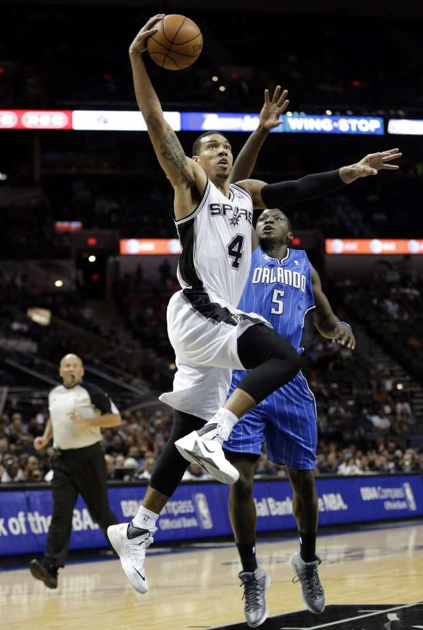 San Antonio Spurs' Danny Green (4) drives past Orlando Magic's Victor Oladipo to score during the first half of a preseason NBA basketball game, Tuesday, Oct. 22, 2013, in San Antonio. Photo: Eric Gay, Associated Press