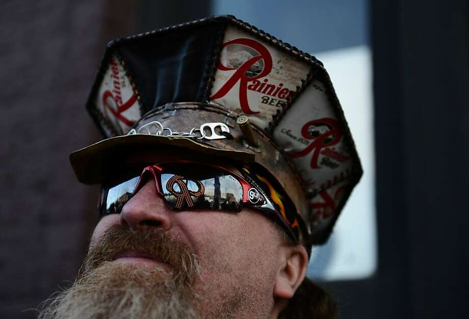 """Zeek """"Built"""" Warzecha smiles as he looks out at the """"R"""" sign, reflected in his sunglasses, during the first stop of the Rainier Beer """"R Crawl"""" at 9 LB Hammer in Georgetown, Wash. on Tuesday, Oct. 22, 2013. Before its restoration to the top of the old Rainier Brewery on Thursday, the sign is taking a tour of the city on a flatbed trailer, making stops at Georgetown, Lower Queen Anne, Ballard, Fremont, Belltown and Capitol Hill, where residents can take photos with it. (AP Photo/The Seattle Times, Lindsey Wasson)  MAGS OUT; NO SALES; SEATTLEPI.COM OUT; MANDATORY CREDIT Photo: Lindsey Wasson, Associated Press"""