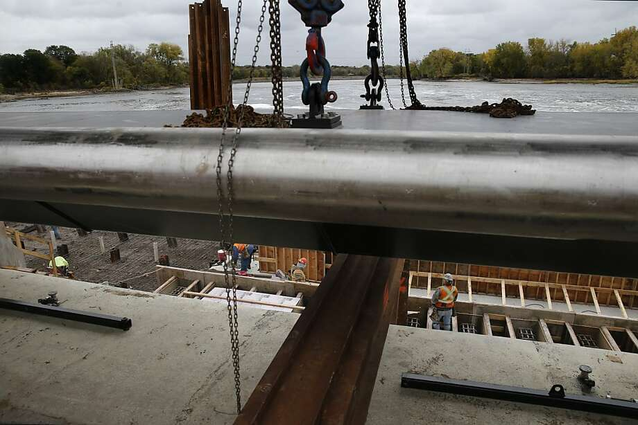 Construction workers install gates at the Cood Rapids dam on Oct. 20, 2013 in Coon Rapids, Minn. The work is a part of a $16 million improvement project to prevent Asian carp from leaping over the dam and reaching the upper Mississippi watershed. The Minnesota Department of Natural Resources said a dead silver carp was recently found at a dam north of Winona, the furthest upstream the fish has been discovered in the Mississippi River.  The nine gates, including six 97-footers, will replace aging rubber tube gates, which are less effective when it comes to keeping fish from passing during serious flooding. The crew is trying working fast before conditions get too icy and cold. (AP Photo/The Star Tribune, Richard Tsong-Taatarii)  MANDATORY CREDIT; ST. PAUL PIONEER PRESS OUT; MAGS OUT; TWIN CITIES TV OUT Photo: Richard Tsong-Taatarii, Associated Press