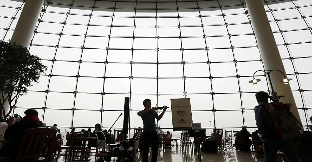 Classical violinist Daniel Butman plays against a backdrop of a multi-story window socked-in with fog in the central terminal at Seattle-Tacoma International Airport Tuesday, Oct. 22, 2013, in SeaTac, Wash. The Seattle-area has endured days of day-long fog, with forecasts through the week of morning fog followed by cloudy afternoons, with temperatures topping out in the mid-50's. (AP Photo/Elaine Thompson)