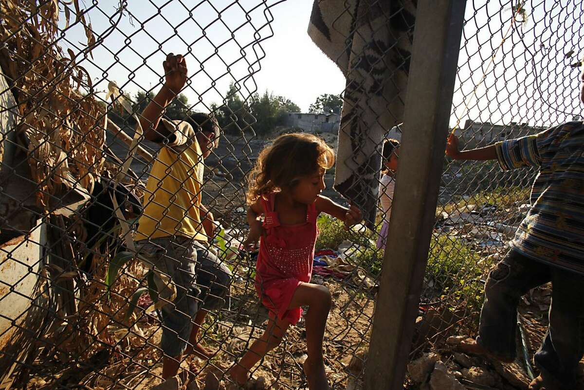 In this Tuesday, Oct. 1, 2013 photo, Heba Alwadiya, 6, passes through a hole made in a fence to gain access to her family house in Gaza City. Their family's only form of transportation is a donkey cart. (AP Photo/Adel Hana)