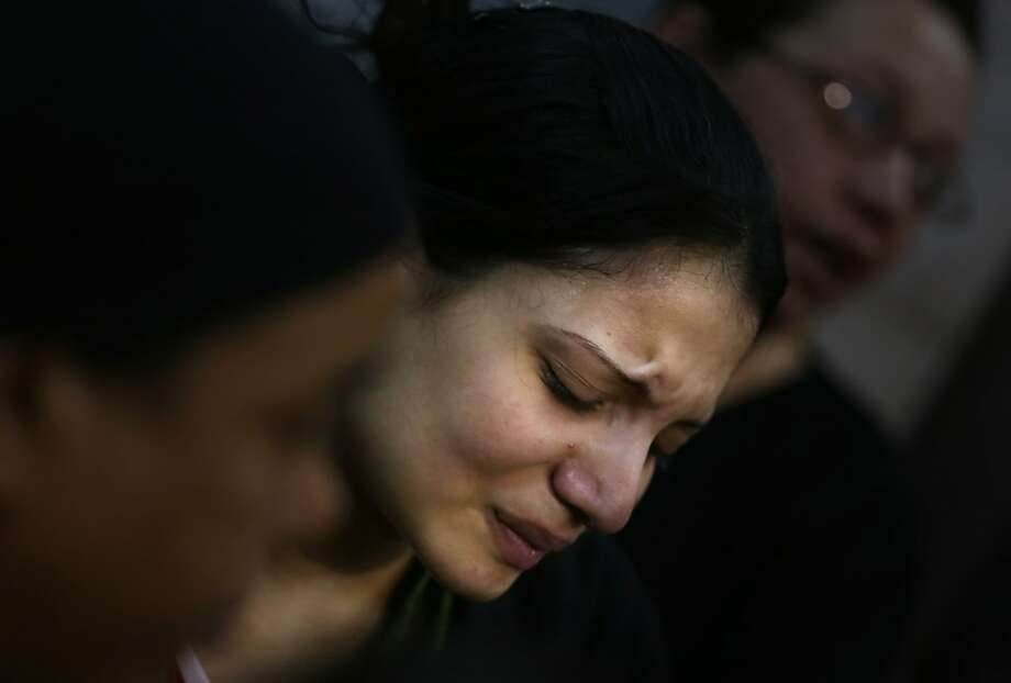 An Egyptian woman mourns during the funeral of several Copt Christians who were killed late Sunday, in Warraq's Virgin Mary church in Cairo, Egypt, Monday, Oct. 21, 2013. Egypt's Christians were stunned Monday by a drive-by shooting in which masked gunmen sprayed a wedding party outside a Cairo church with automatic weapons fire, killing several, including two young girls, in an attack that raised fears of a nascent insurgency by extremists after the military's ouster of the president and a crackdown on Islamists. (AP Photo/Khalil Hamra) Photo: Khalil Hamra, Associated Press
