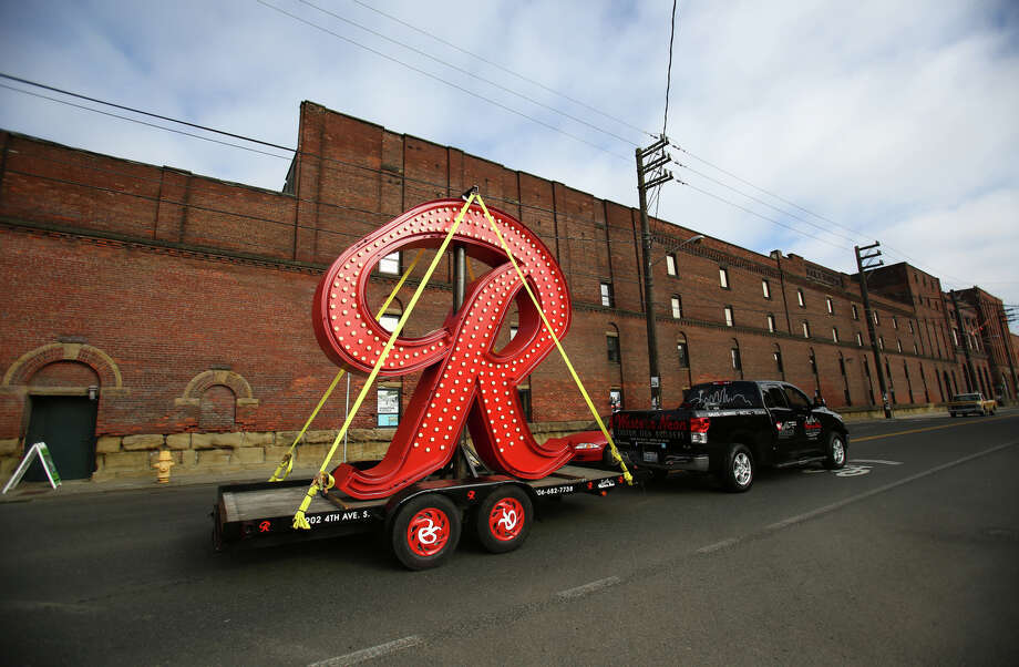 "A new Rainier Beer ""R"" passes the original Rainier Brewery in Georgetown as it visits Seattle neighborhood bars. The nearly 12-foot tall sign was traveling in advance of its installation on top of the former Rainier Brewery in Sodo. The ""R"" will replace the Tully's green ""T"" that was previously on the building. Photographed on Tuesday, Oct. 22, 2013. Photo: JOSHUA TRUJILLO, SEATTLEPI.COM / SEATTLEPI.COM"