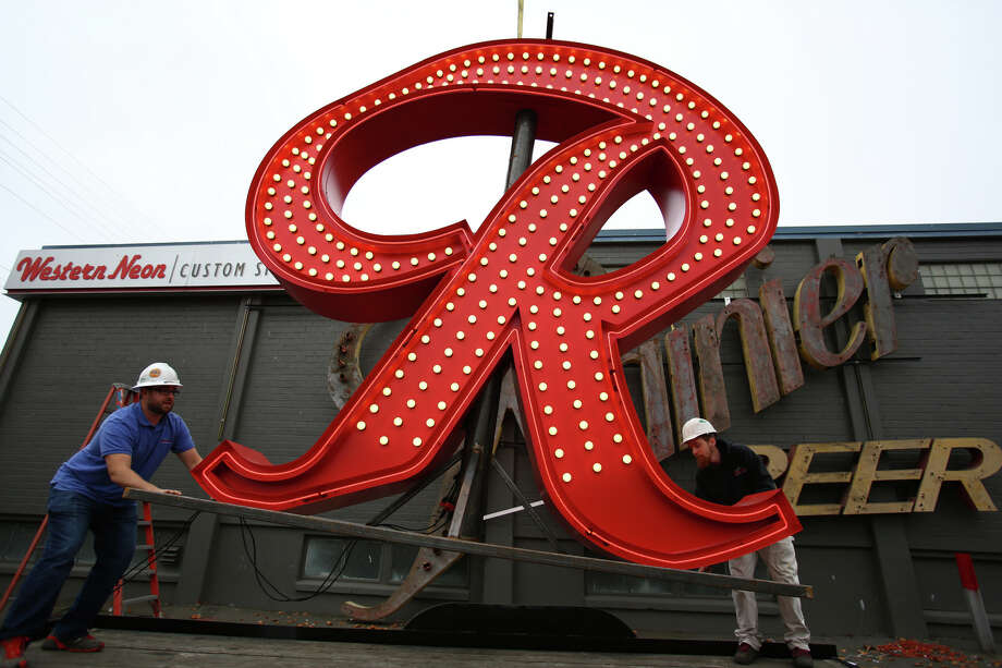 "Andre Lucero, left, and Zach Velkoff of Western Neon hoist a new Rainier ""R"" onto a trailer. The nearly 12-foot tall, 1,100 pound sign was traveling in advance of its 