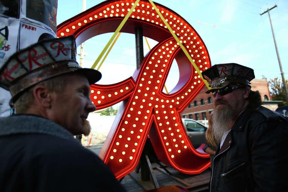 "Brothers Zeek, left, and Stan Warzecha look over a new Rainier Beer ""R"" as it visits Georgetown. Photo: JOSHUA TRUJILLO, SEATTLEPI.COM / SEATTLEPI.COM"