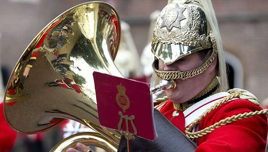 Tourists are reflected in the brass of a member of the Life Guards band as they escort a Colour party of the Grenadier Guards as they leave St James's Palace to change the guard at Buckingham Palace in London, Wednesday, Oct. 23,2013. Prince William and his wife Kate have asked seven people to be godparents to their son, Prince George, who will be christened at a major royal family gathering Wednesday, palace officials said. Photo: Alastair Grant, Associated Press