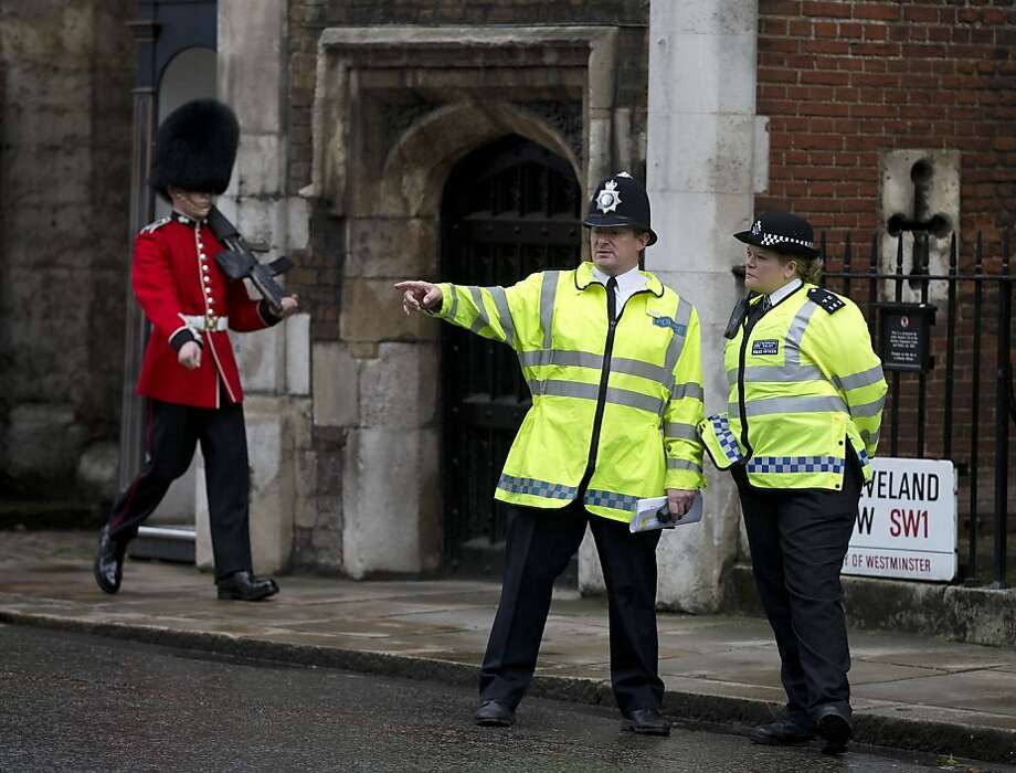 Police officers monitor the small crowd of media and royal fans outside St James's Palace, as a member of the Grenadier Guards marches past in London, Wednesday, Oct. 23, 2013. Prince William and his wife Kate have asked seven people to be godparents to their son, Prince George, who will be christened at a major royal family gathering Wednesday, palace officials said.  Queen Elizabeth II and her husband Prince Philip plan to attend the christening Wednesday at the Chapel Royal at St. James's Palace, along with Prince Charles, his wife Camilla, Prince Harry and other royals. Photo: Alastair Grant, Associated Press