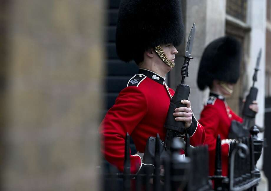 Two members of the Grenadier Guards come to attention outside St James's Palace, in London, Wednesday, Oct. 23, 2013. Prince William and his wife Kate have asked seven people to be godparents to their son, Prince George, who will be christened at a major royal family gathering Wednesday, palace officials said.  Queen Elizabeth II and her husband Prince Philip plan to attend the christening Wednesday at the Chapel Royal at St. James's Palace, along with Prince Charles, his wife Camilla, Prince Harry and other royals. Photo: Alastair Grant, Associated Press