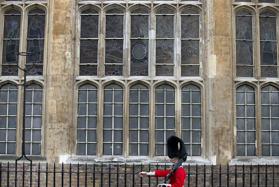 A Grenadier Guard marches past the stained glass windows of the Chapel Royal outside St James's Palace, in London, Wednesday, Oct. 23, 2013. Prince William and his wife Kate have asked seven people to be godparents to their son, Prince George, who will be christened at a major royal family gathering Wednesday, palace officials said.  Queen Elizabeth II and her husband Prince Philip plan to attend the christening Wednesday at the Chapel Royal at St. James's Palace, along with Prince Charles, his wife Camilla, Prince Harry and other royals. Photo: Alastair Grant, Associated Press