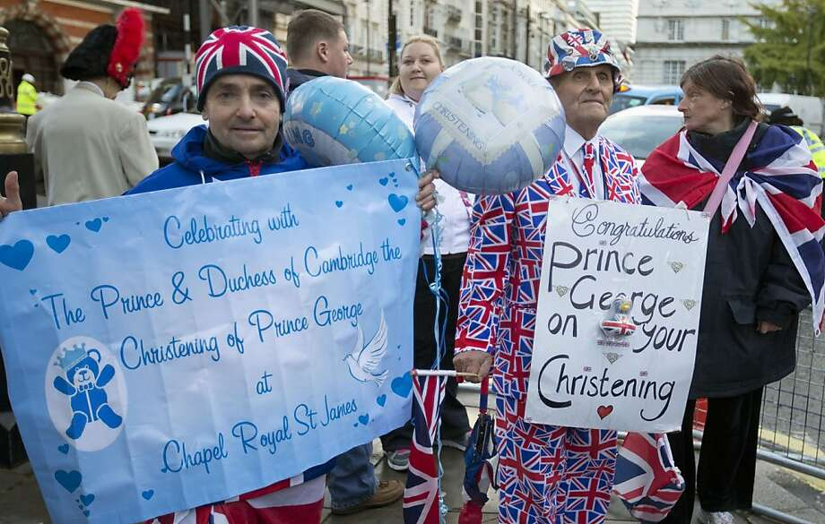 Royal wellwishers gather and display their home made placards and greetings to the media,  as they wait outside St James's Palace, for the christening of Britain's Prince George, in London, Wednesday, Oct. 23, 2013. Prince William and his wife Kate have asked seven people to be godparents to their son, Prince George, who will be christened at a major royal family gathering Wednesday, palace officials said. Photo: Alastair Grant, Associated Press