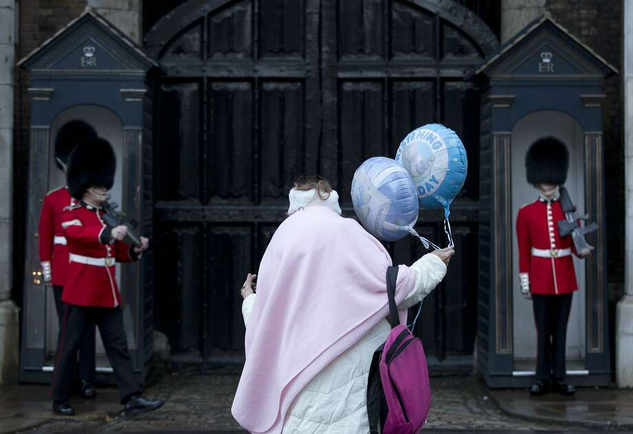 A royal fan holding a christening celebration balloon watches as members of the Grenadier Guards mount guard outside St James's Palace in London, Wednesday, Oct. 23, 2013. Britain's Prince George, son of Prince William and Kate Duchess of Cambridge and who is third in line to the throne will be christened in the Chapel Royal inside the palace Wednesday. Photo: Alastair Grant, Associated Press