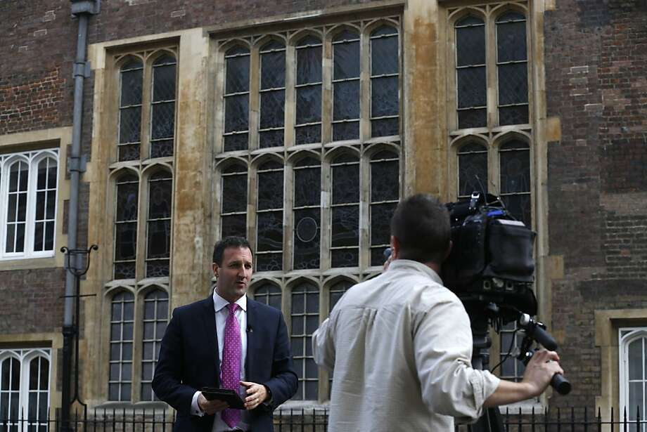 A television crew report from outside the Chapel Royal, St James's Palace in London ahead of the christening of Prince George, Tuesday, Oct. 22, 2013. The royal christening ceremony of Prince George, son of Prince William and Kate, Duchess of Cambridge is to take place at the Chapel on Wednesday. Photo: Sang Tan, Associated Press