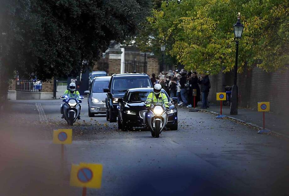 The car carrying Britain's Prince William, the Duchess of Cambridge and their son Prince George, is escorted by police as it drives from Kensington Palace on the way to St. James Palace for the christening of Prince George. Britain's 3-month-old future monarch, Prince George will be christened Wednesday with water from the River Jordan at a rare four-generation gathering of the royal family in London. Photo: Lefteris Pitarakis, Associated Press