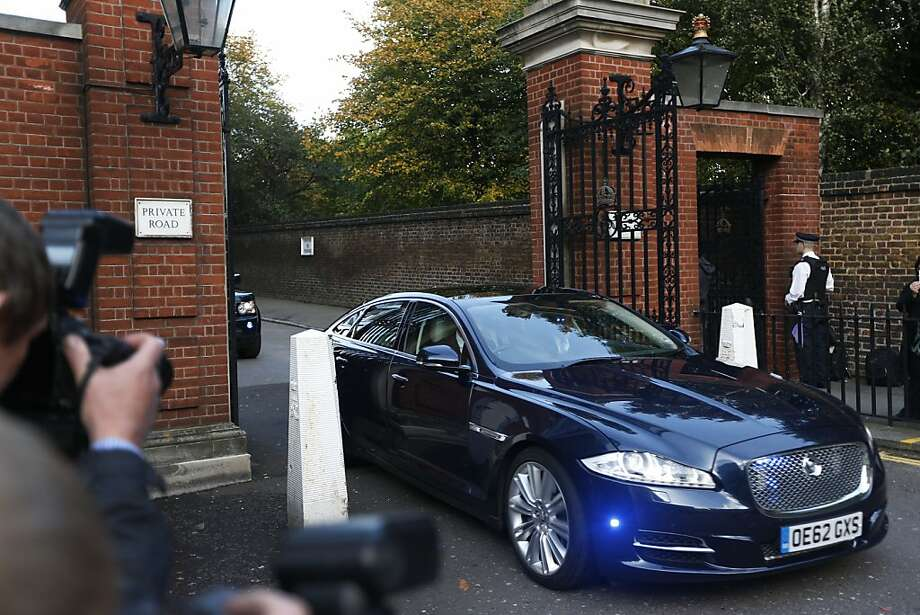 The car carrying Britain's Prince William, the Duchess of Cambridge and their son Prince George, leaves from Kensington Palace on the way to St. James Palace for the christening of Prince George. Britain's 3-month-old future monarch, Prince George will be christened Wednesday with water from the River Jordan at a rare four-generation gathering of the royal family in London. Photo: Lefteris Pitarakis, Associated Press