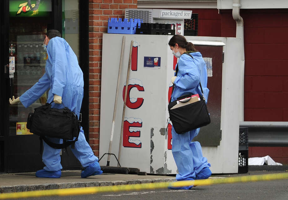 Wearing protective suits, masks, and gloves, police enter the scene at Patriot Fuels at 719 Boston Post Road in Milford, Conn. where a robbery suspect was shot and killed by a state police officer early Wednesday morning, October 23, 2013. The covered body of the suspect lies under a white sheet behind the ice machine at right. Photo: Brian A. Pounds / Connecticut Post