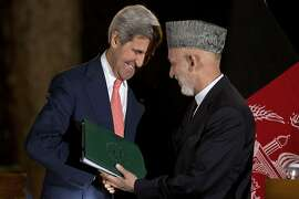 US Secretary of State John Kerry (L) shakes hands with Afghan President Hamid Karzai after a press conference at the Presidential Palace during an unannounced stop in Kabul on October 12, 2013. Karzai and Kerry held a second day of talks in Kabul after making progress over a long-delayed deal on the future of US forces in Afghanistan. AFP PHOTO/POOL/ JACQUELYN MARTINJACQUELYN MARTIN/AFP/Getty Images